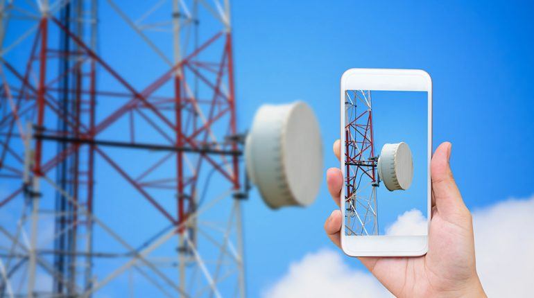 hand hold mobile smartphone with telecommunication tower and satellite antennas wireless technology on blue sky background